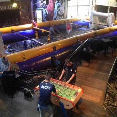 Baby foot humain gonflable dans un bar d'ambiance